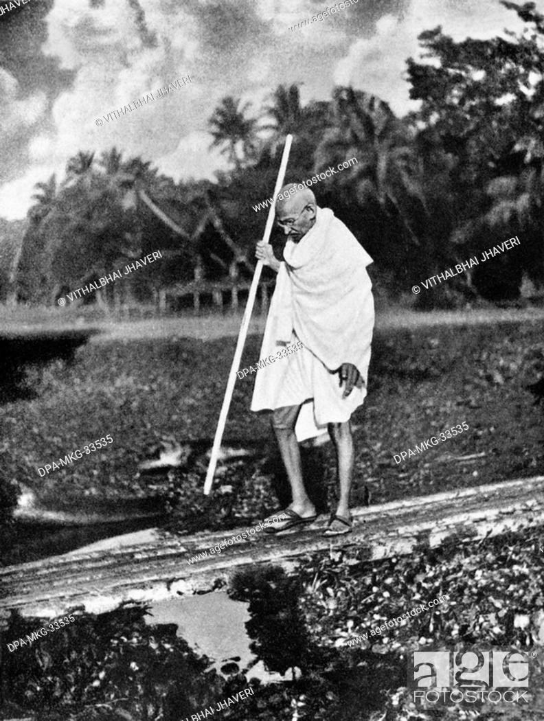 Stock Photo: Mahatma Gandhi walking in Noakhali West Bengal, India, November 1946 - MODEL RELEASE NOT AVAILABLE.
