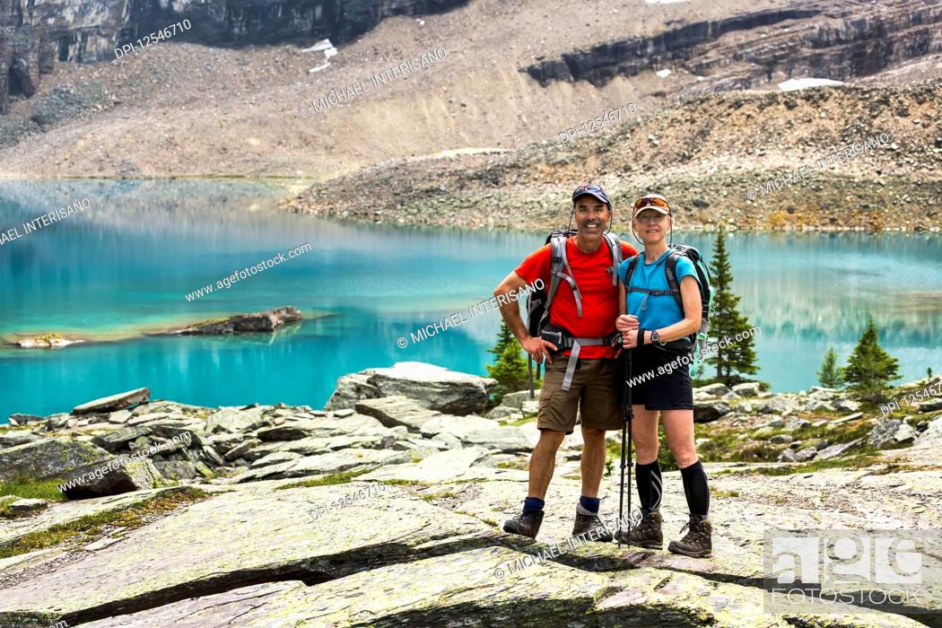 Imagen: Female and male hiker standing in a large rocky area with colourful alpine lake and mountain cliffs in the background; British Columbia, Canada.