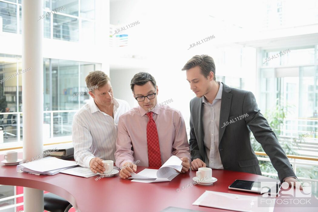 Stock Photo: Business colleagues meeting over red table.