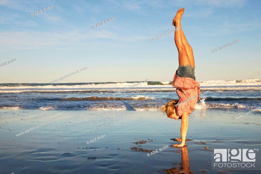 Stock Photo: Girl doing handstand on the beach.