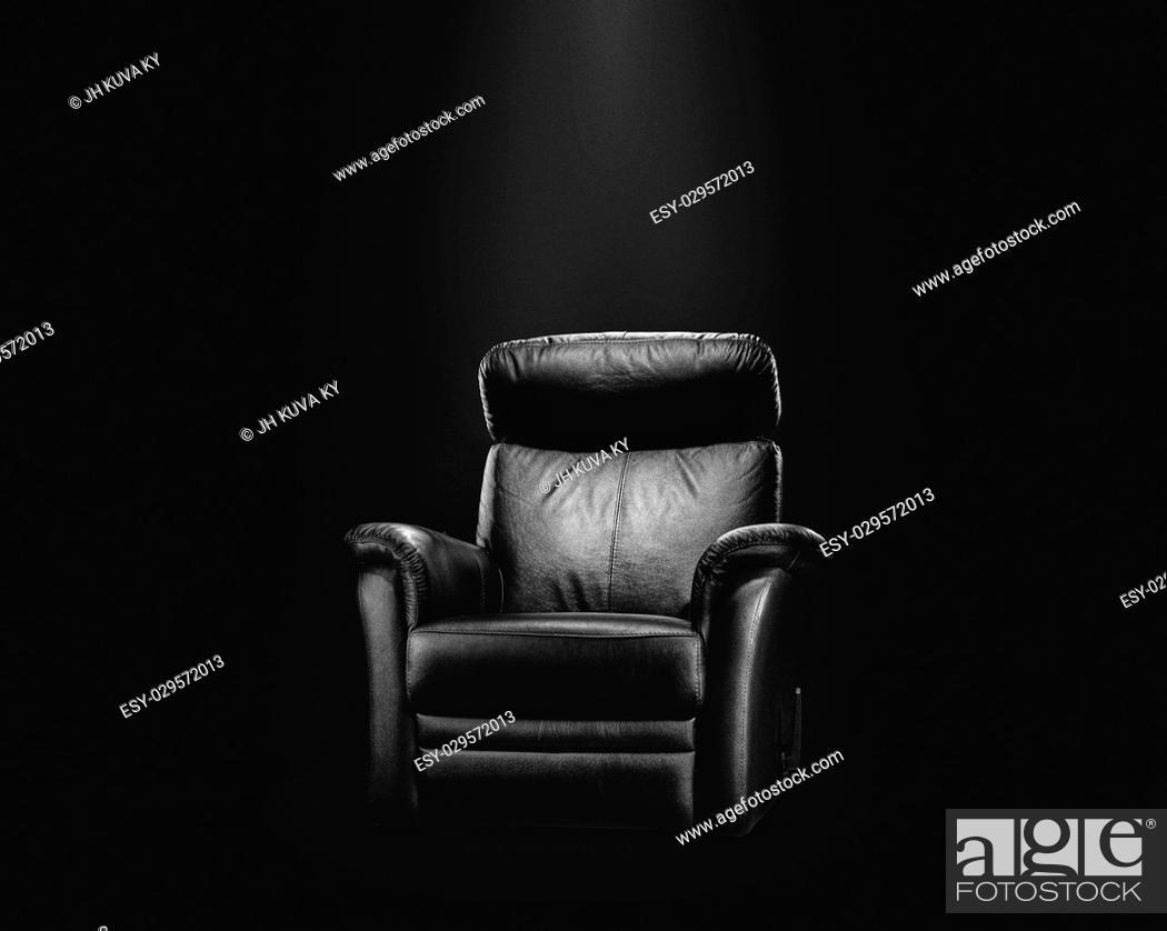 Stock Photo: Black leather armchair in spotlight, dark background.