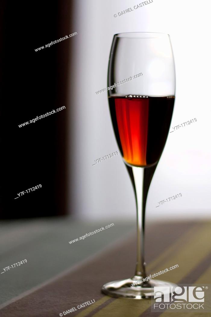 Stock Photo: Liquor crystal glass on stripped table.