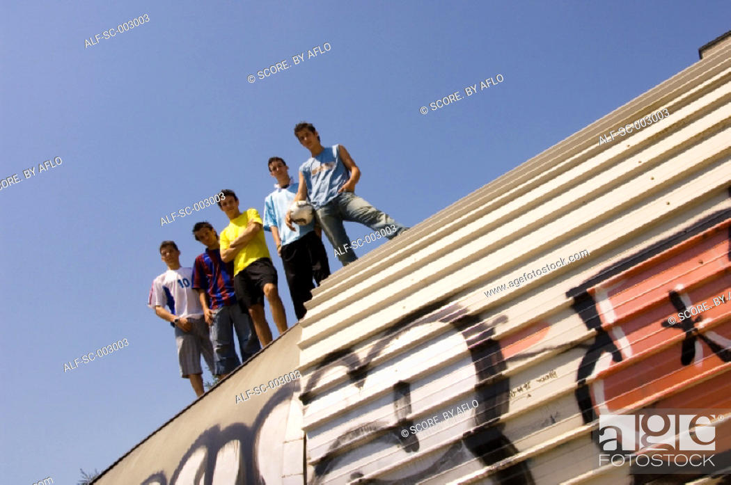 Stock Photo: Group of teenage soccer friends on roof of tunnel.