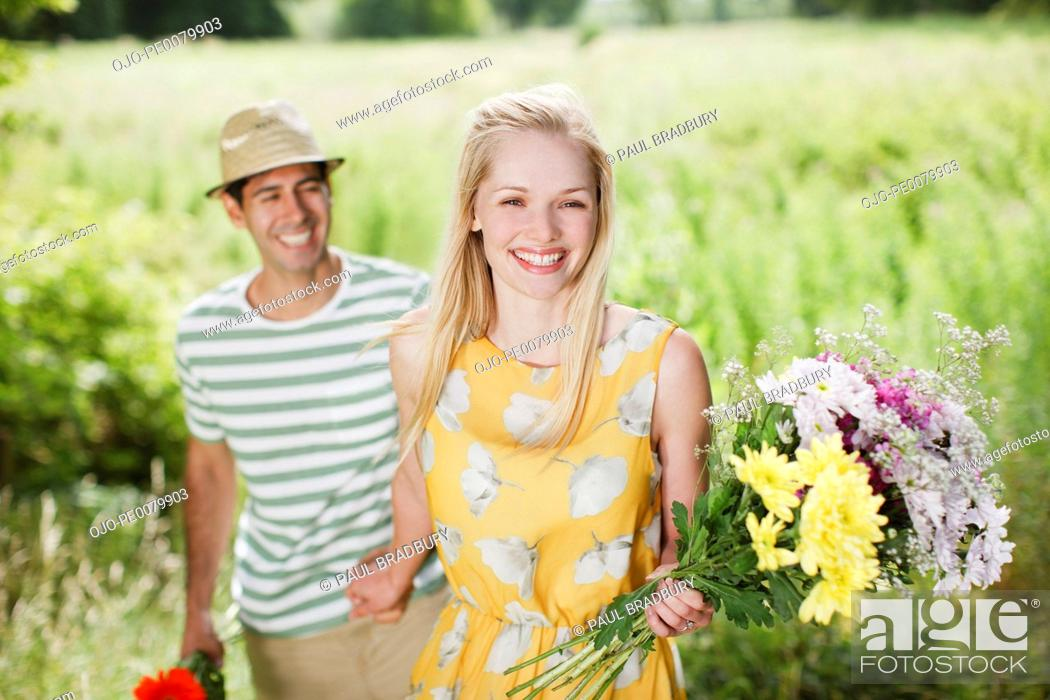 Stock Photo: Smiling couple with flowers in rural field.