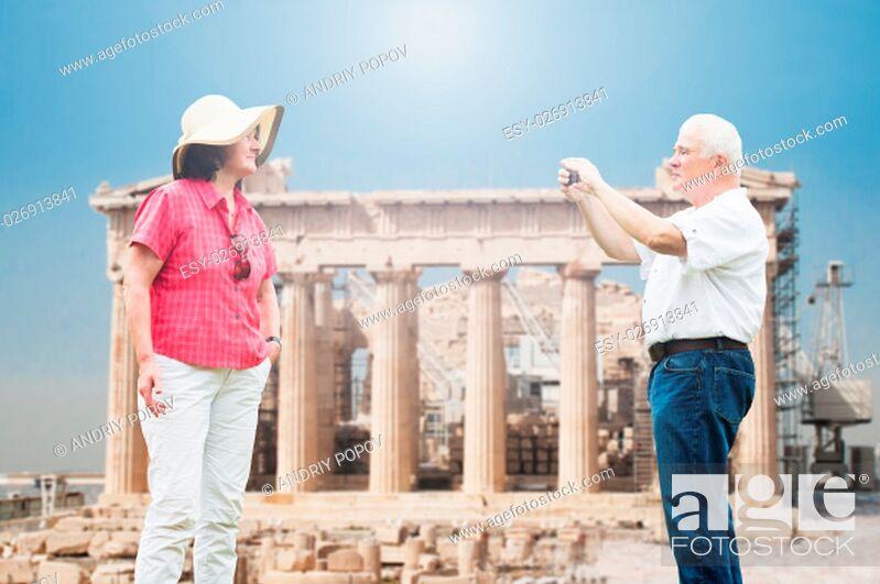 Stock Photo: Senior Man Taking Photograph Of His Wife Against Parthenon Temple.