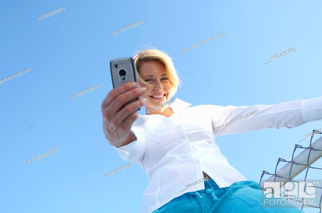 Imagen: Mirando A La Cámara, Pelo Corto, Primer Plano, Teléfono Móvil, Mediana Edad, Plano Americano, Vista Desde Abajo, Color, Solamente, Uno, Exteriores, Retrato, Adulto, Raza Blanca, Mujer, Feliz, Sonrisa, Horizontal, Vista, Cielo, Etnia, Rubio, Hobby, Portátil, Tecnología, Fotografía, Blanco, Comunicación, Célula, Celulares