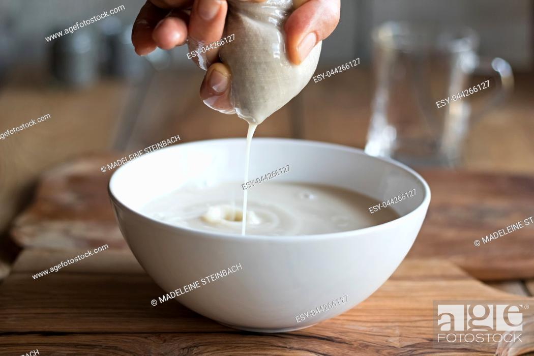Stock Photo: Preparation of nut milk - straining the milk through a milk bag into a bowl.