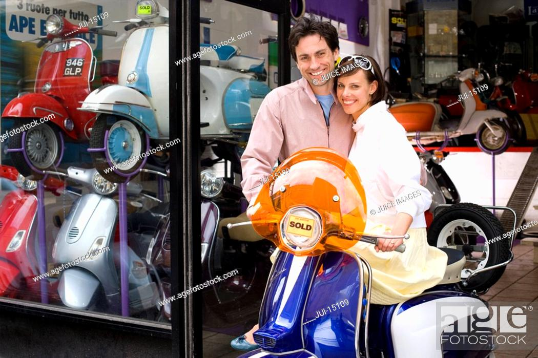 Stock Photo: Couple purchasing scooter, smiling, portrait.