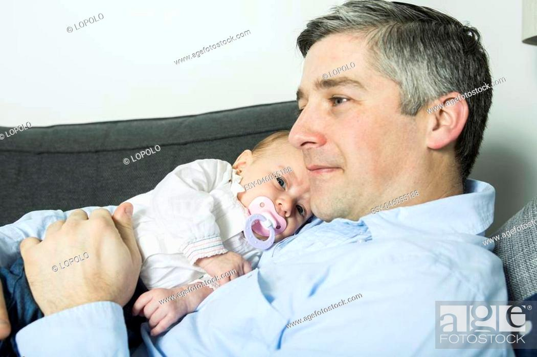 Imagen: A Father holding up baby girl lying on sofa, side view.