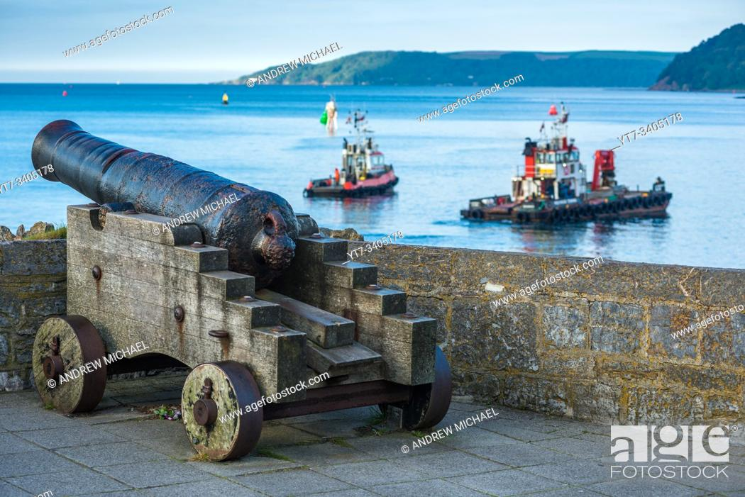 Stock Photo: A restored 19th century Blomefield design cast iron cannon points across the water as boats passby, on Plymouth seafront in south Devon, UK.