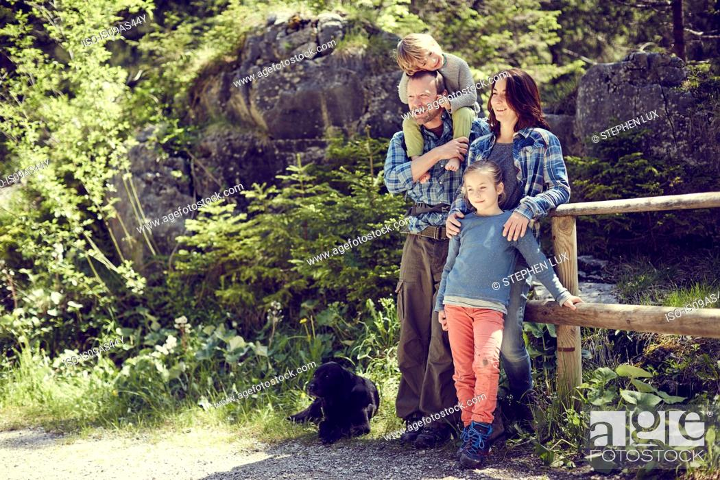 Imagen: Portrait of family, in forest, standing by fence.