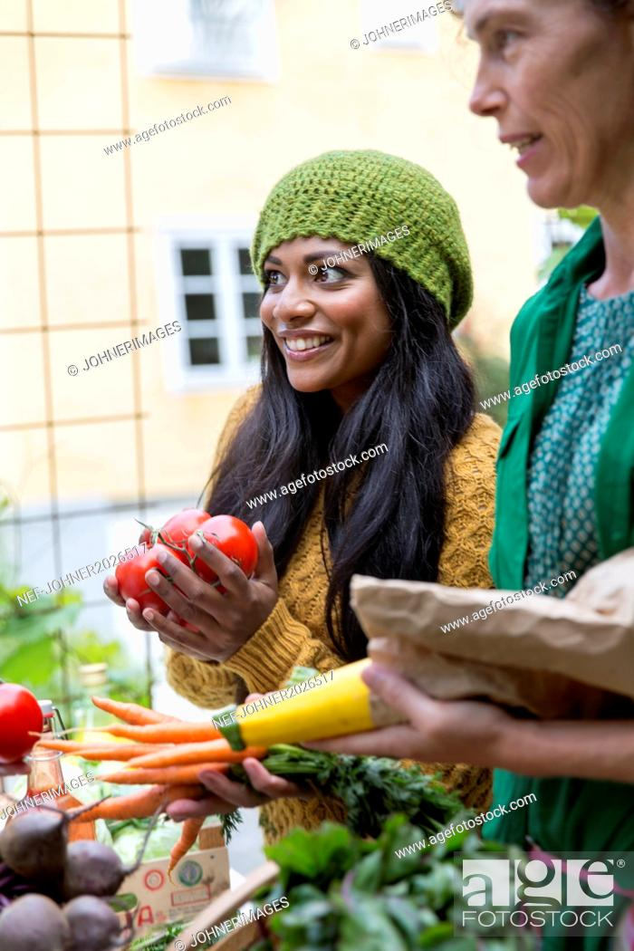 Stock Photo: Young women buying home-grown vegetables.