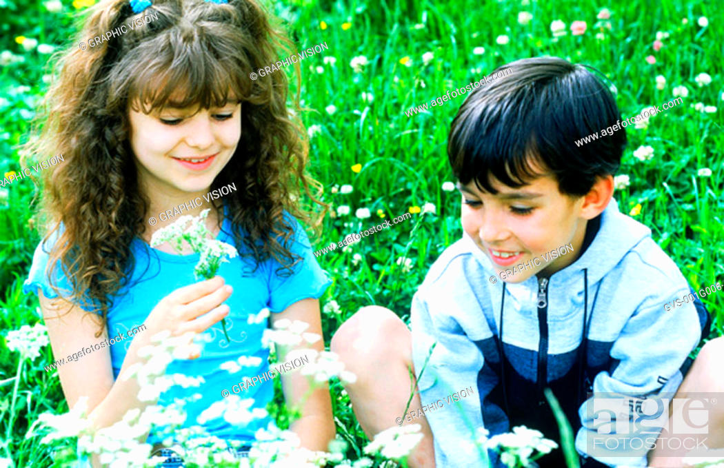 Stock Photo: Young boy and young girl picking flowers.