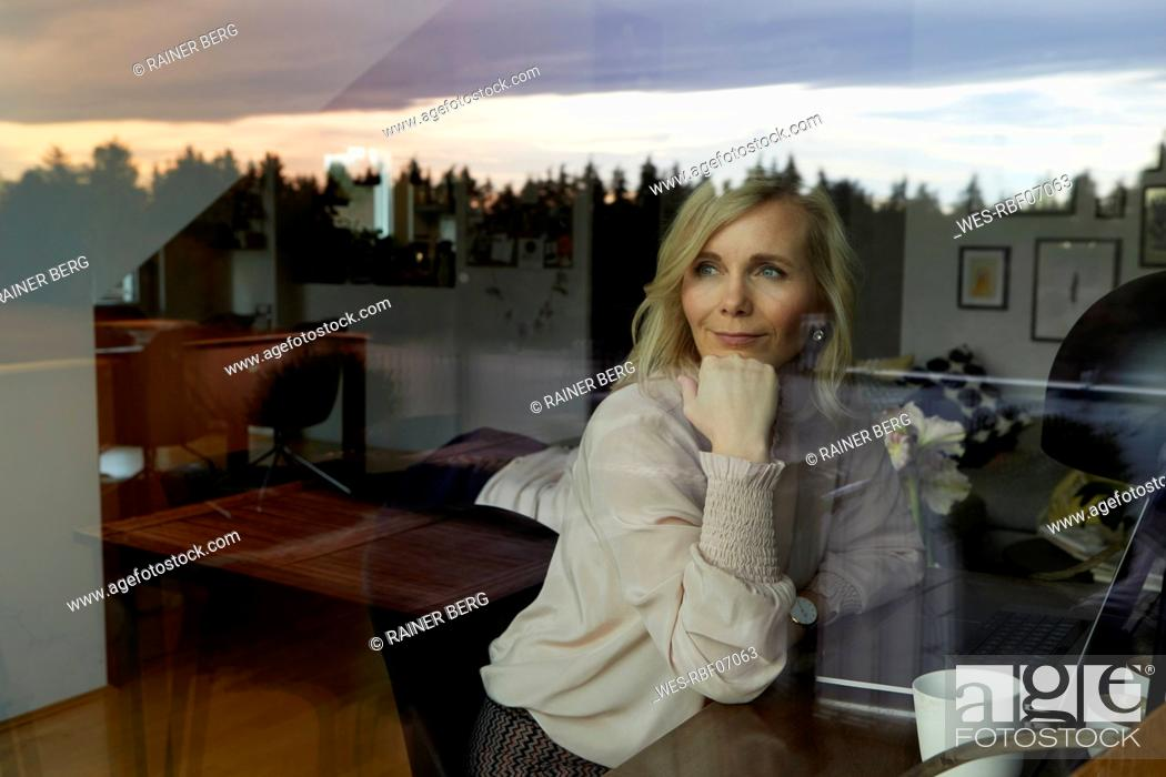 Imagen: Portrait of blond woman with laptop behind windowpane at home.
