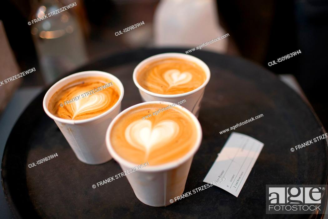 Stock Photo: Three takeaway cups of coffee with heart shaped tops.