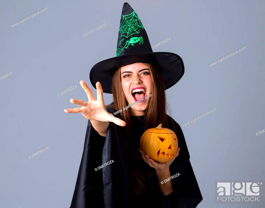 Stock Photo: Beautiful young woman in black costume of witch with black hat holding a pumpkin and holding hand in front of her on blue background in studio.