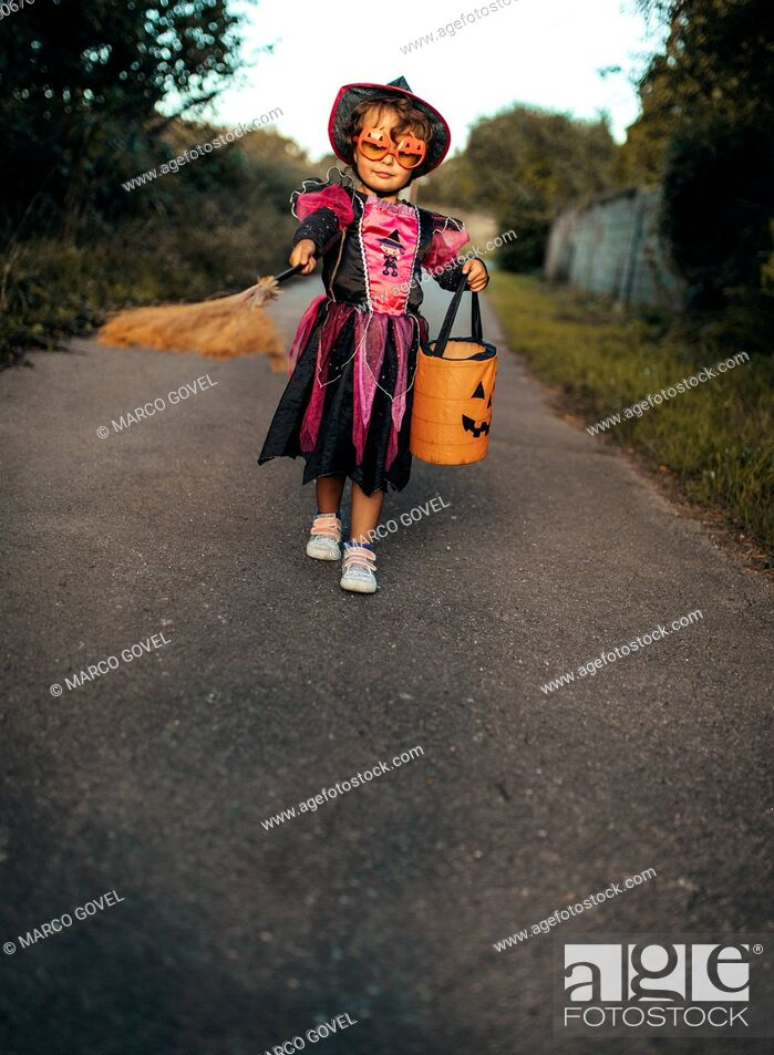 Stock Photo: Little girl masquerade as a witch with halloween lantern and broom.