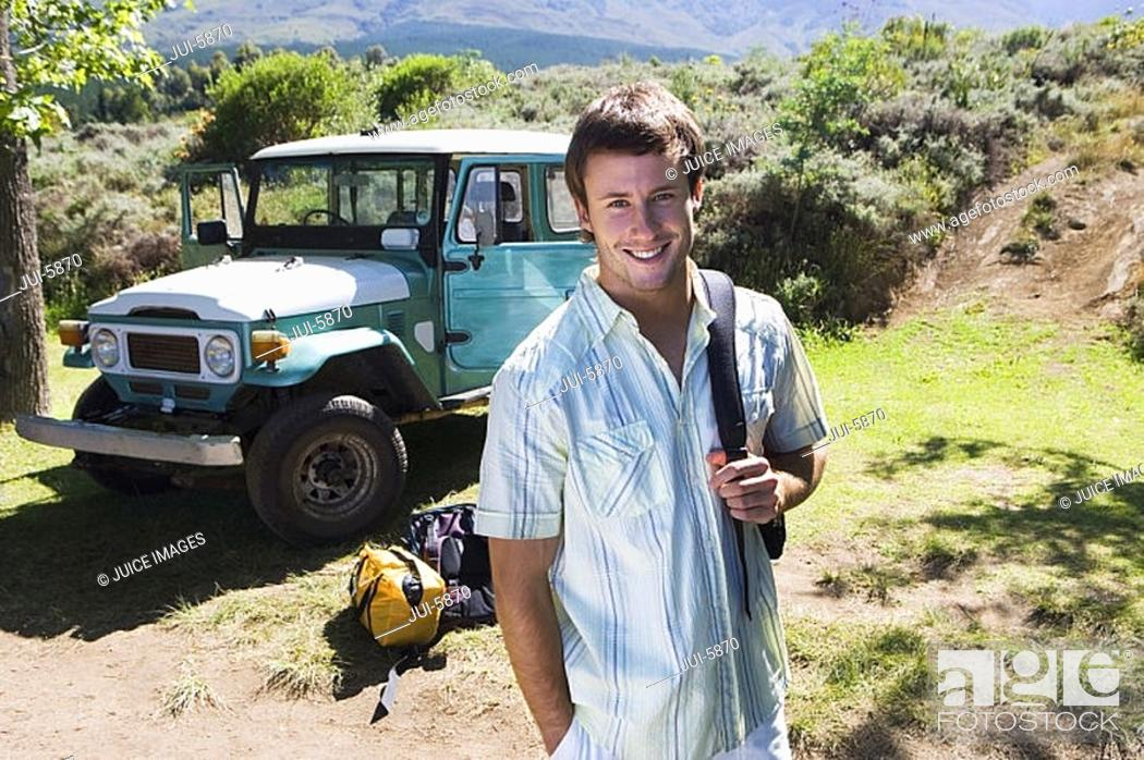 Stock Photo: Young man standing near parked jeep at start of camping holiday, carrying rucksack, smiling, portrait.