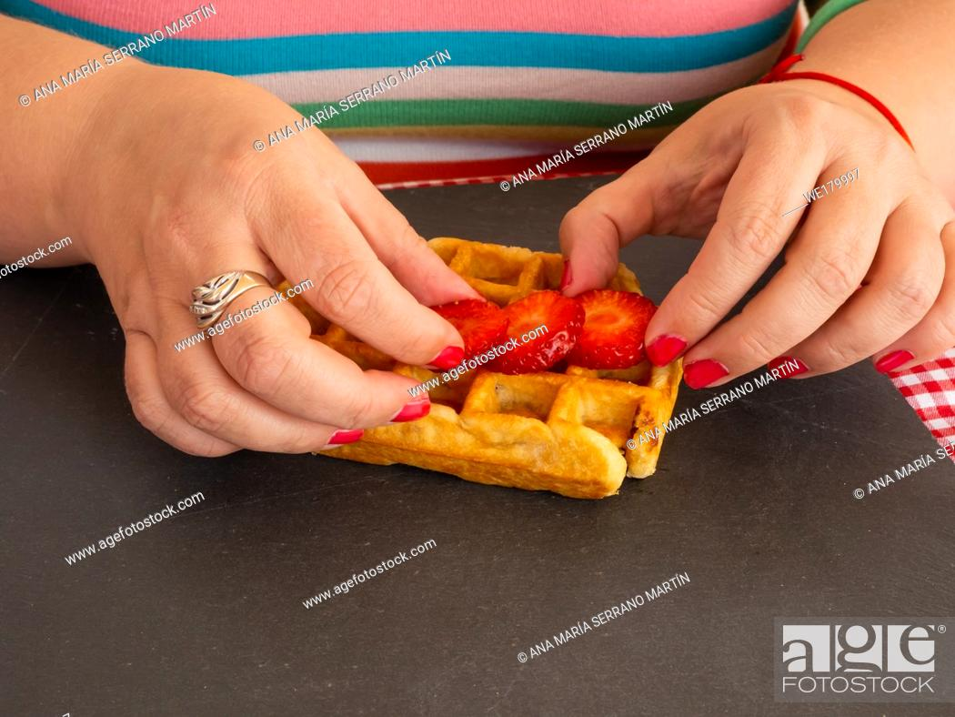 Stock Photo: A woman with red fingernails placing strawberry pieces on a Belgian waffle.