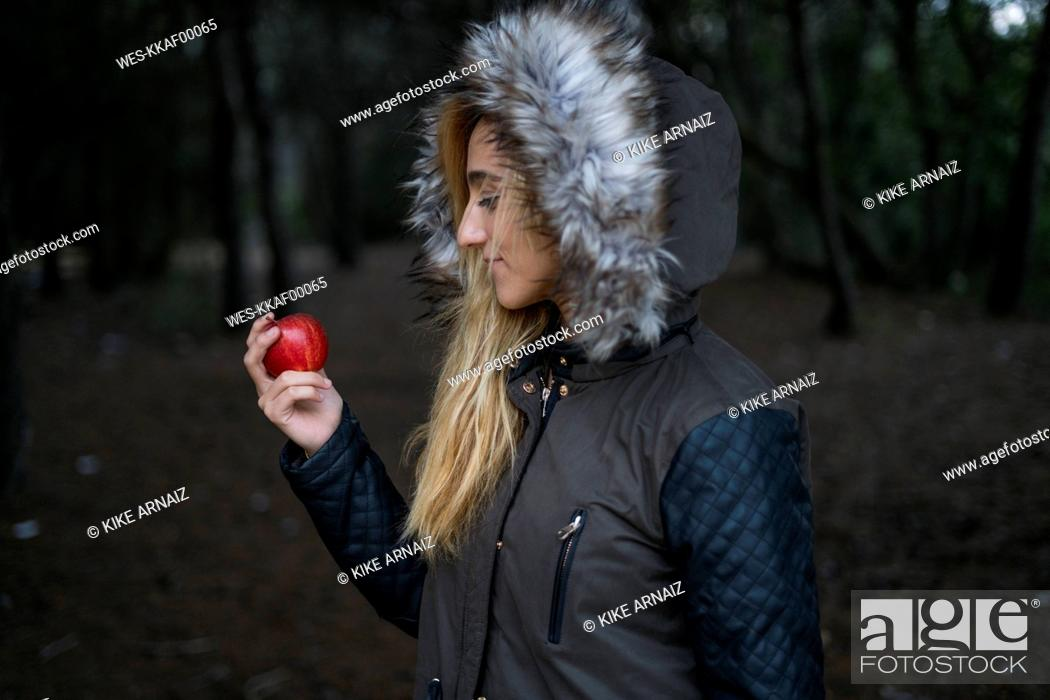 Stock Photo: Young woman with red apple wearing hooded jacket.