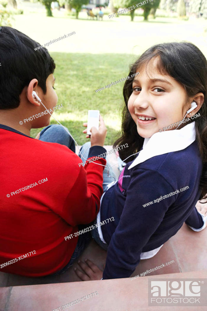 Stock Photo: Portrait of a girl and her brother listening to an MP3 player.