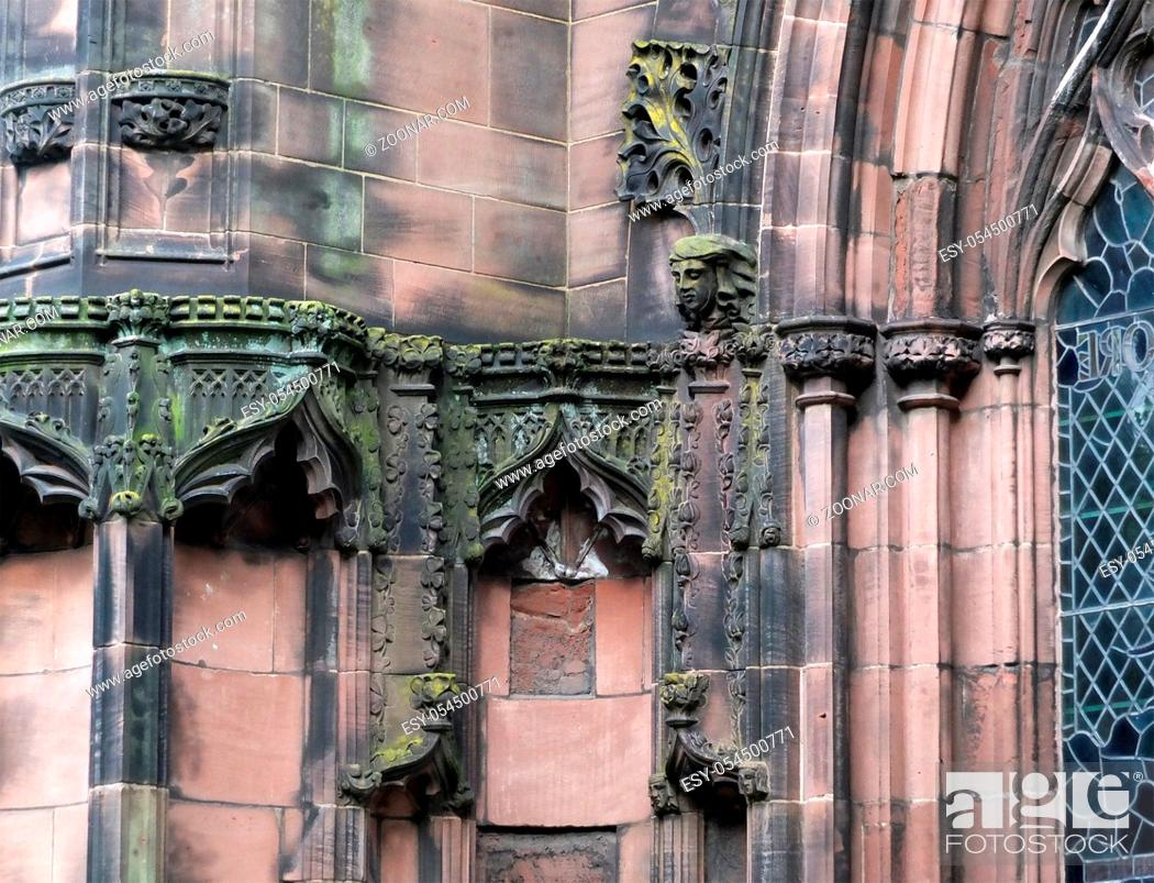 Stock Photo: details of ornately carved medieval stonework with niches and faces on the facade of chester cathedral.