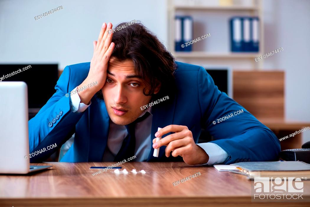 Stock Photo: The young man having problems with narcotics at workplace.