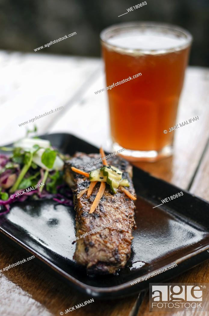 Stock Photo: marinated grilled barbecue pork rib with salad and pickled vegetables set with michelada cocktail drink.