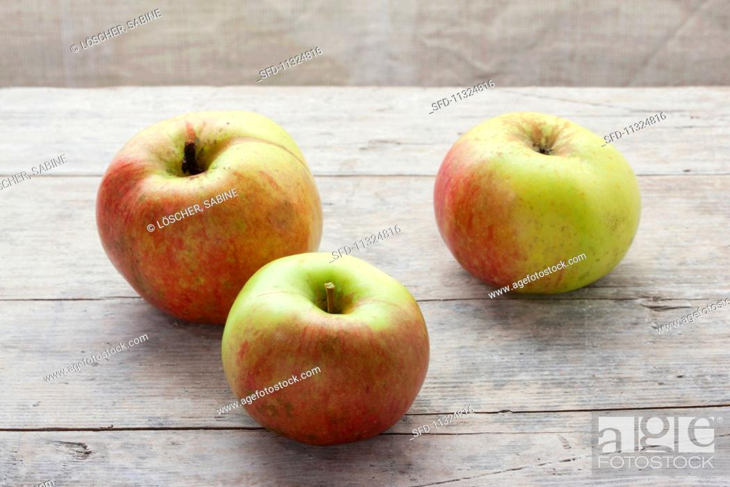 Stock Photo: Three organic Ontario apples on a wooden surface.