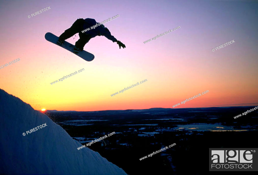 Stock Photo: Silhouette of person performing stunt on snowboard.