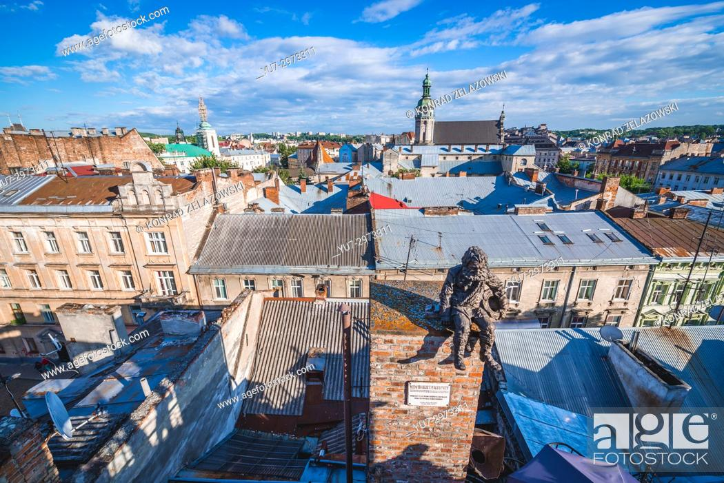 Stock Photo: Chimney sweeper statue on the roof of famous restaurant House of Legends on the Old Town of Lviv, Ukraine. Former Bernardine church and monastery on background.