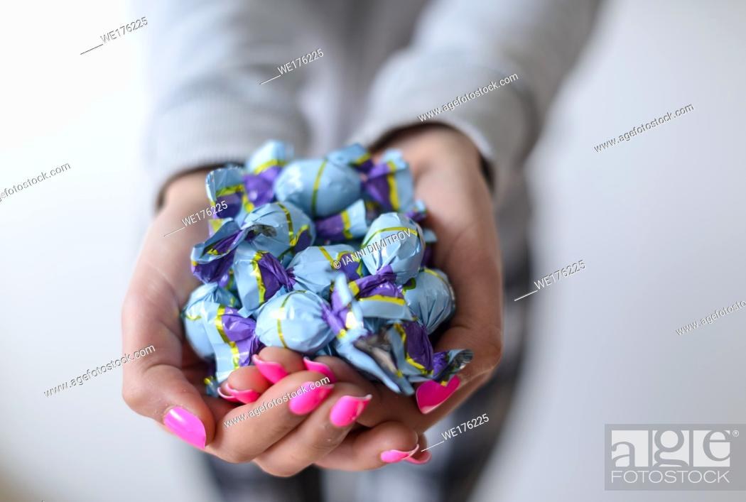Stock Photo: Selective focus-Girl with pink nail varnish hold wrapped chocholate sweets.