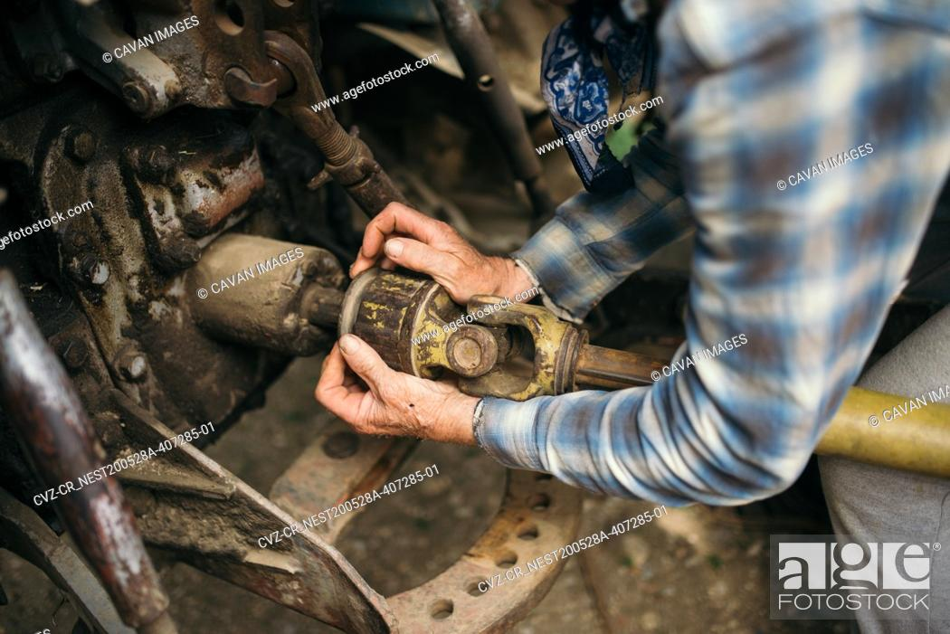 Photo de stock: A mechanic is repairing a tractor used in agriculture closeup.