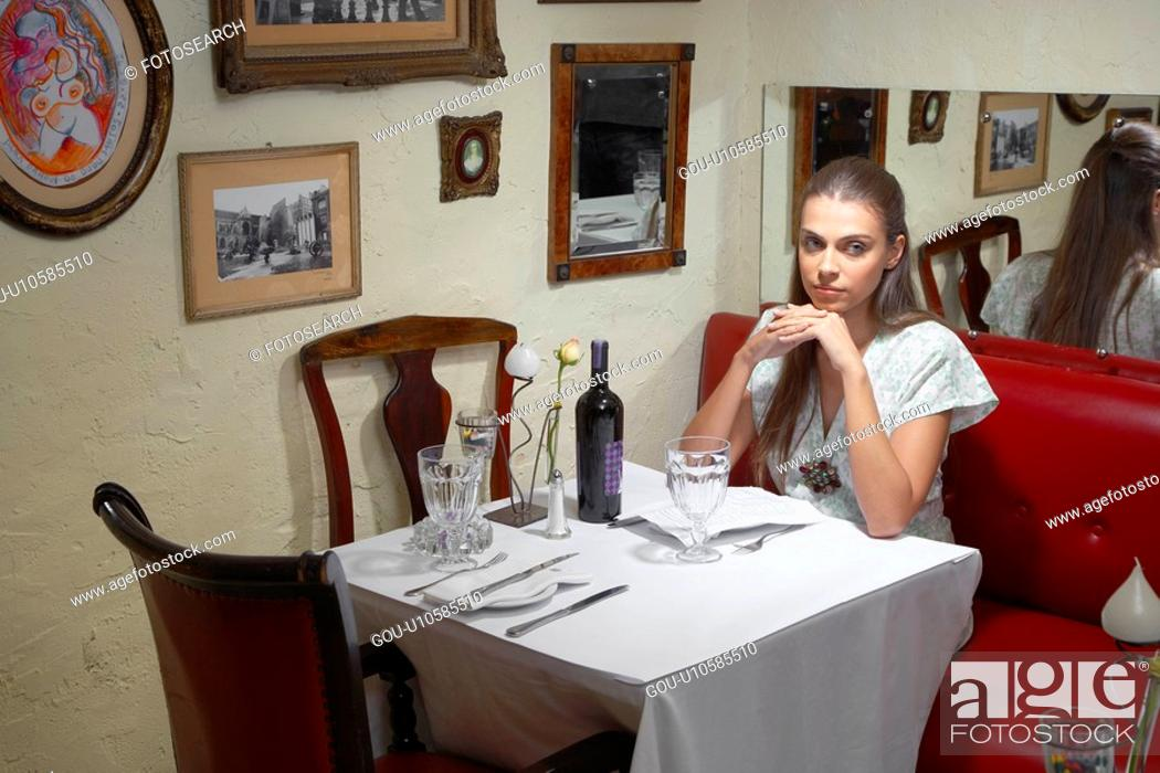 Stock Photo: Woman sitting at dining table in restaurant.