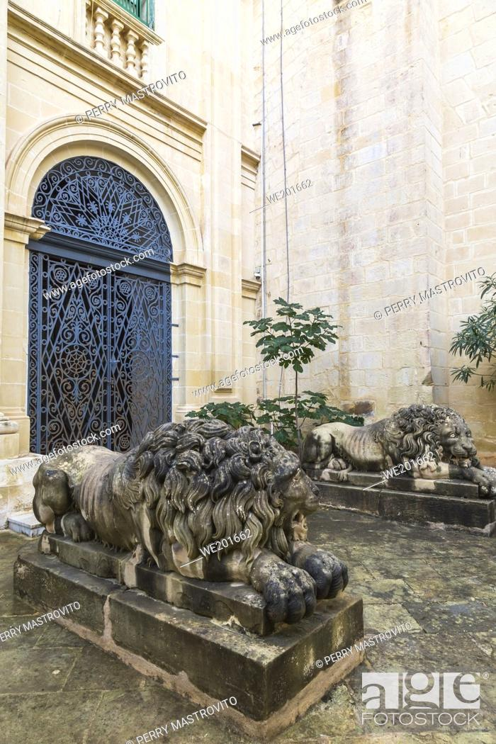 Stock Photo: Carved limestone lion sculptures and arched entrance door with ornate wrought iron grills, Garden of the Grand Masters Palace, Valletta, Malta.