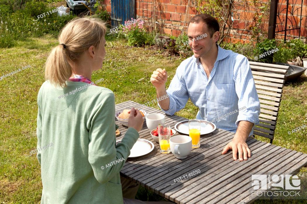 Stock Photo: A couple enjoying breakfast in their backyard.