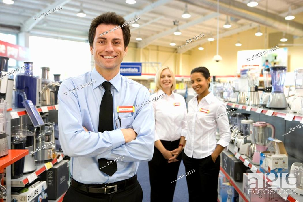 Stock Photo: Young salesman with arms crossed, colleagues in background, smiling, portrait.