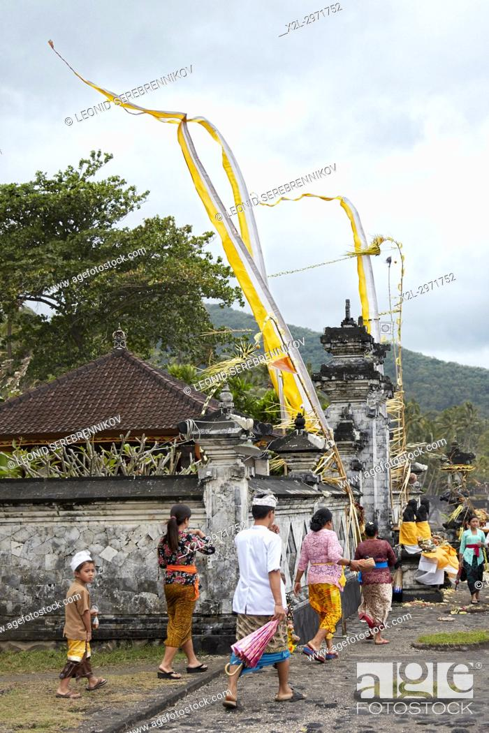 People Wearing Traditional Balinese Clothing In Front Of A