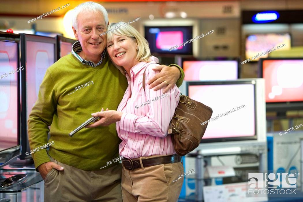 Stock Photo: Mature couple arm in arm, shopping for television, smiling, portrait.