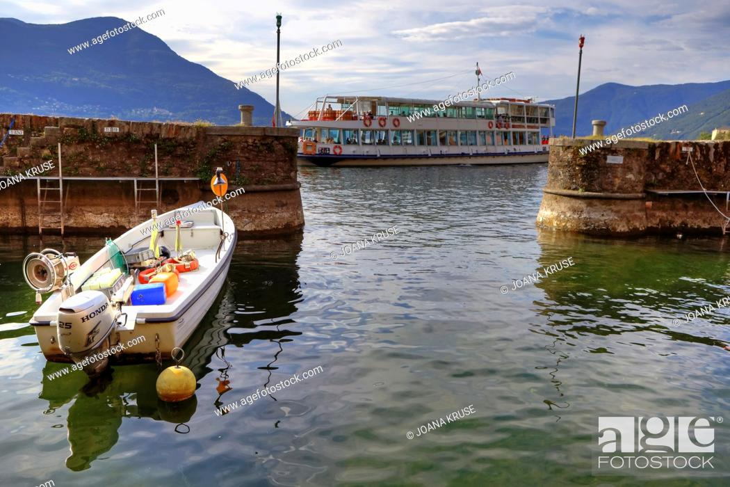Stock Photo: the small, ancient port of Brissago line with a boat in the background.