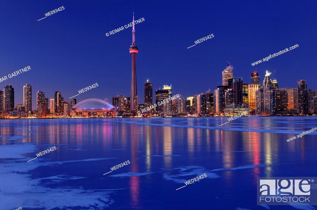 Stock Photo: Frozen ice covered Lake Ontario reflecting the lights of Toronto city skyline at dusk.