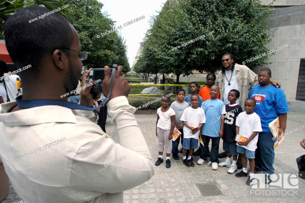 """Imagen: Etan Thomas of the Washington Wizards poses for a picture with fans during the DC Hip Hop Theatre Festival, during the Fest's """"Poetry Slam""""."""