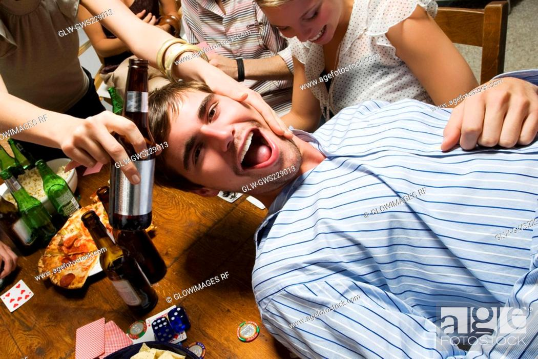Stock Photo: Young man with his friends enjoying a party.