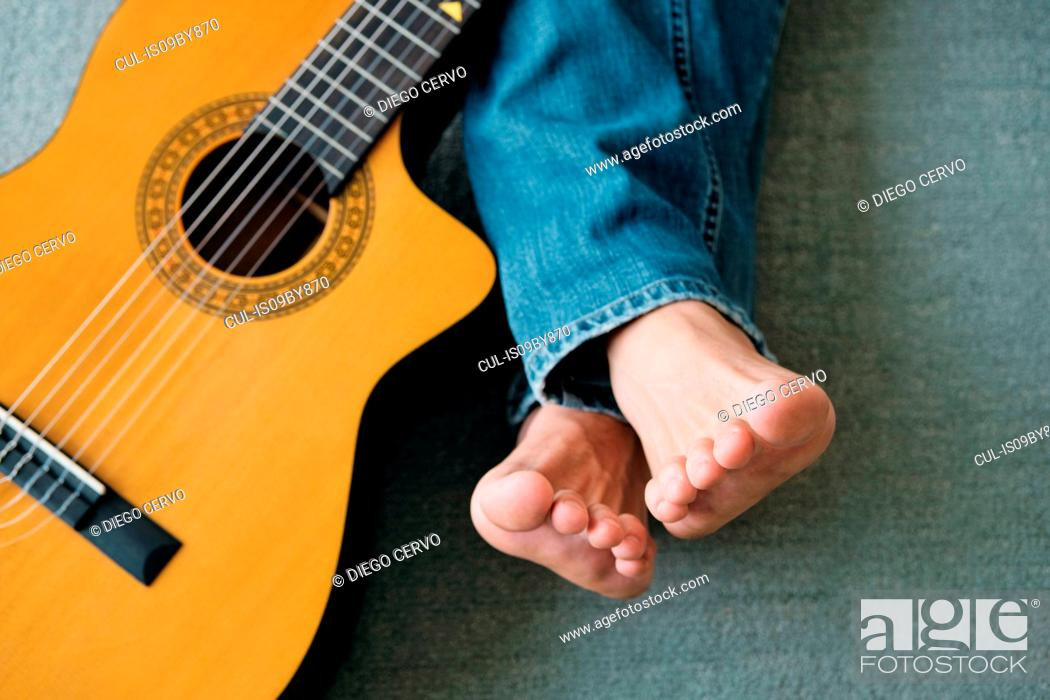 Photo de stock: Guitarist with legs outstretch beside guitar on floor.