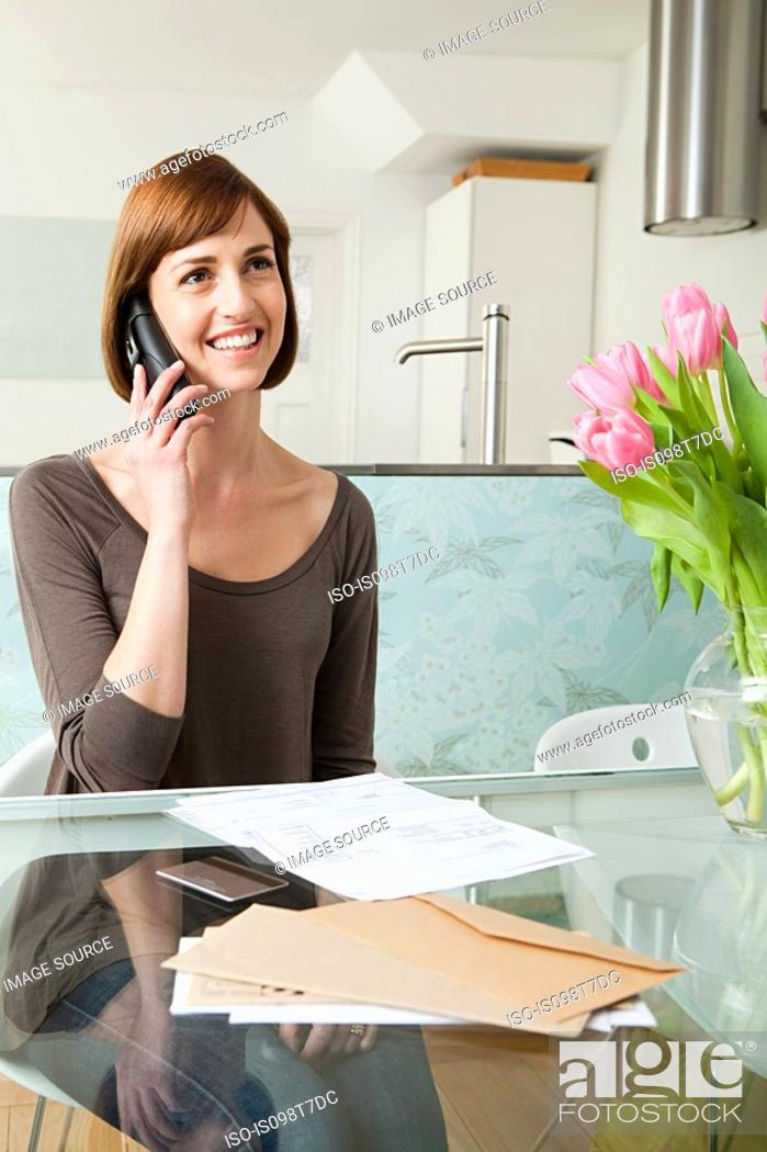 Stock Photo: Woman on telephone with bills.