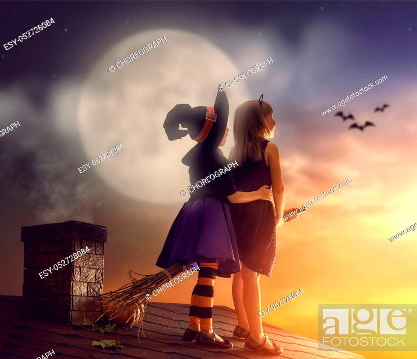 Stock Photo: Two happy sisters on Halloween. Funny kids in carnival costumes on the roof with broomstick. Cheerful children looking at moon.