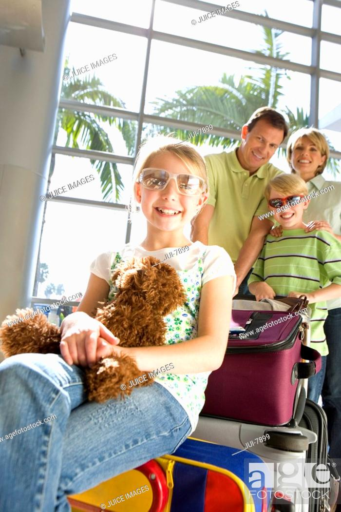 Stock Photo: Family standing beside luggage trolley in airport, girl 7-9, in sunglasses, sitting on suitcase with soft toy in foreground, smiling, front view, portrait tilt.