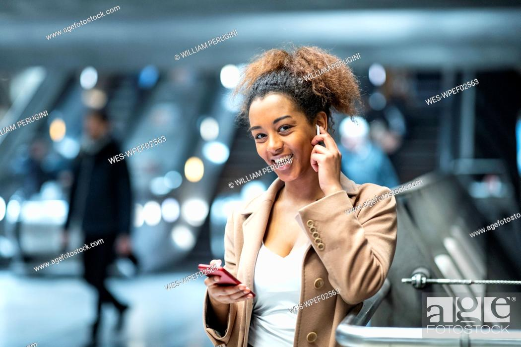 Stock Photo: Portrait of happy young woman with cell phone and earbuds at subway station.