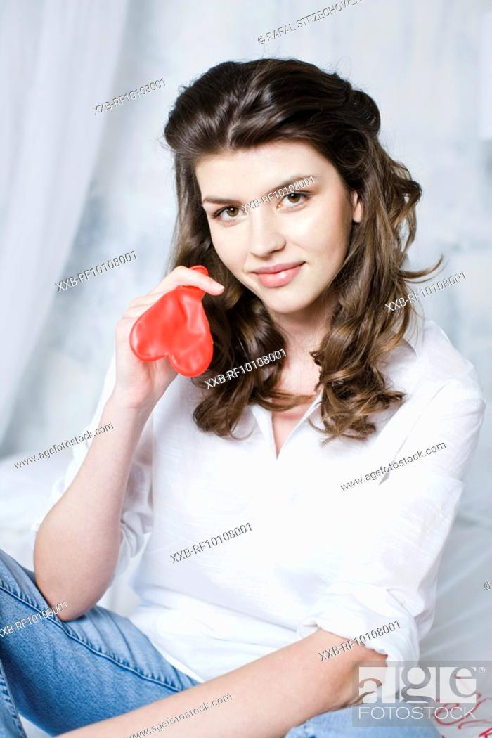 Stock Photo: Woman blowing up balloon.