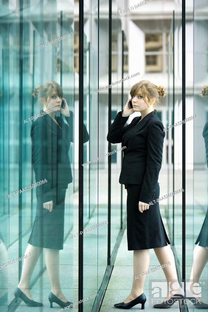Stock Photo: Businesswoman using cell phone, looking nervously at camera.